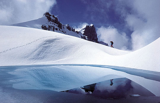 Mountaineer walking across snowy mountain